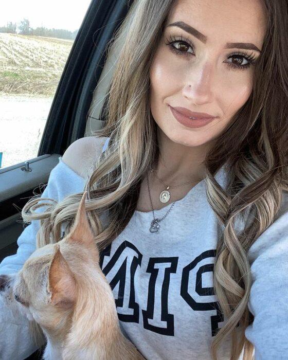 Mujer sentada en su auto sosteniendo a su perrito en brazos