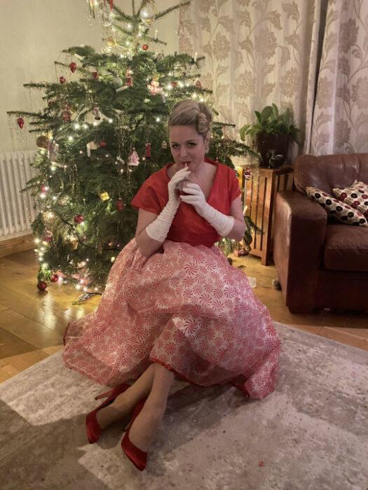 Rosie Chandler usando un vestido de color rosa mientras está sentada frente al árbol