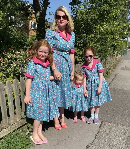 Rosie Chandler and her daughters wearing similar dresses in shades of blue and pink
