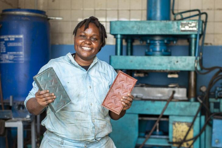 Mujer sosteniendo ladrillo de plástico entre sus manos; Mujer keniana convierte el plástico de un solo uso en ladrillos más fuertes que el concreto