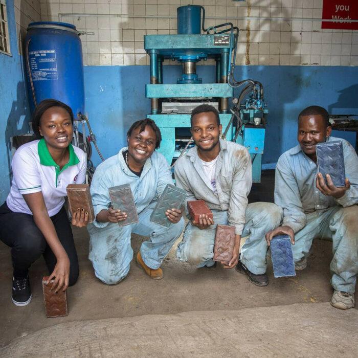 grupo de amigos sosteniendo ladrillos de plástico; Mujer keniana convierte el plástico de un solo uso en ladrillos más fuertes que el concreto