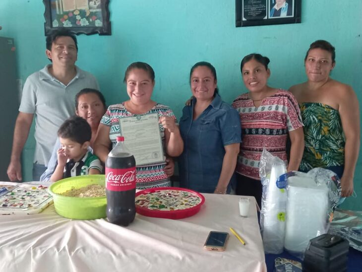 Mujer sosteniendo su acta de divorcio junto a su familia y festejando