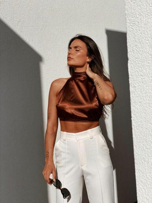 Chica usando una blusa de satín de color café