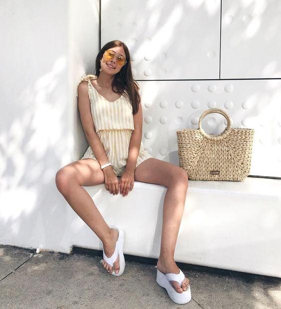 Chica usando unas sandalias flip flops con un short