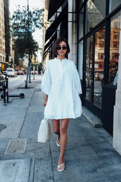 Chica usando unas sandalias flip flops con un vestido camisero blanco