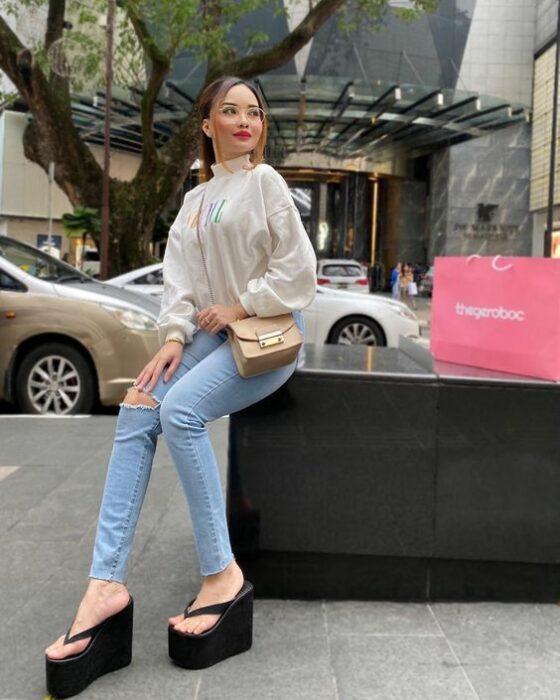 Chica usando unas sandalias flip flops con un pantalón y camisa blanca