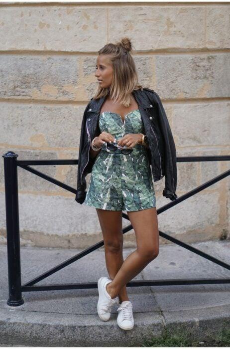 Chica usando un jumpsuit de color vede con tenis blancos