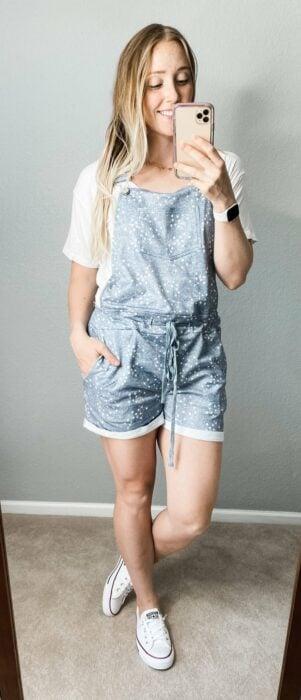 Chica usando un jumpsuit de color mezclilla con tenis blancos