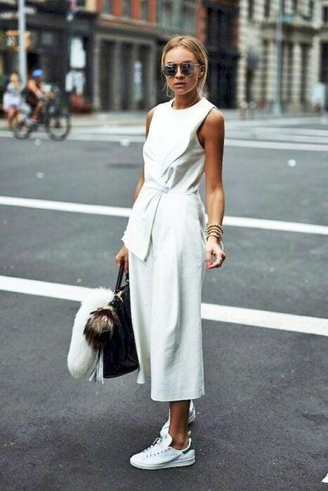 Chica usando un jumpsuit de color blanco con tenis blancos