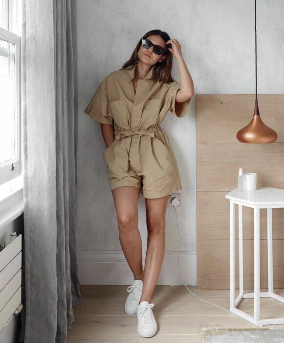 Chica usando un jumpsuit de color café con tenis blancos y lentes de sol