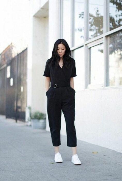Chica usando un jumpsuit de color negro con tenis de color blanco