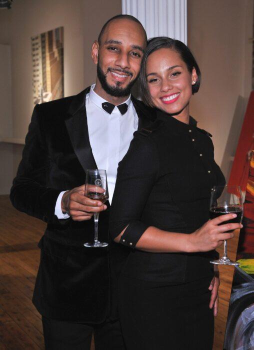 Alicia Keys y Swizz Beatz posando juntos mientras toman una copa