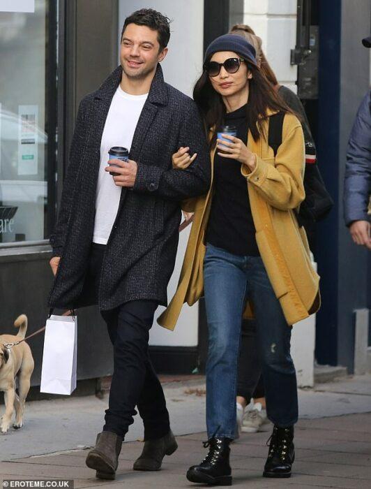 Gemma Chan y Dominic Cooper dando un paseo mientras están tomados del brazo