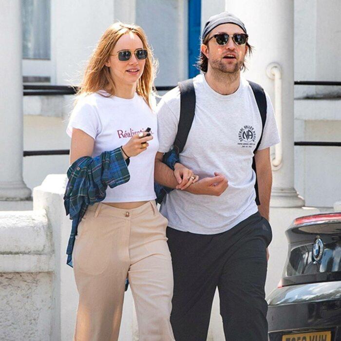 Suki Waterhouse y Robert Pattinson caminando juntos y tomados de los brazos