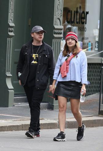 Georgia Groome y Rupert Grint caminando mientras van tomados de la mano