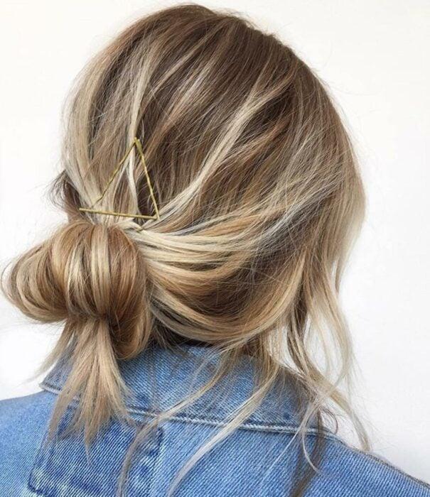 Chica con el cabello hasta los hombros sujetado con un chonguito y pasadores
