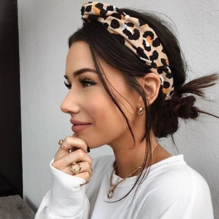 Girl with shoulder-length hair fastened with a headband and a low bun