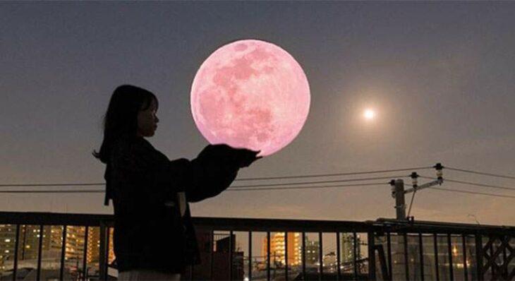 Mujer que aparenta sostener una superluna rosa en sus manos