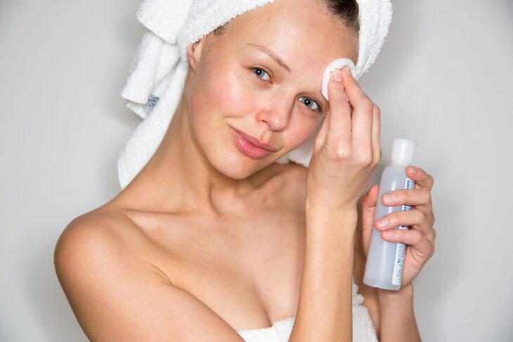 Chica usando un tónico para limpiar su rostro