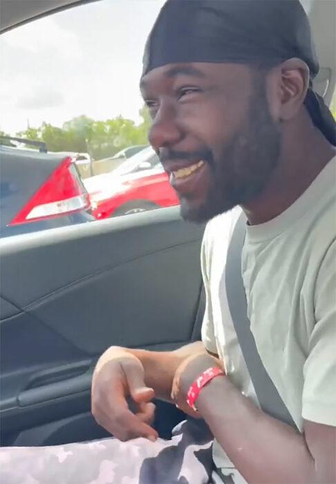 Hombre sin hogar sentado en el asiento de un auto sonriendo feliz y emocionado
