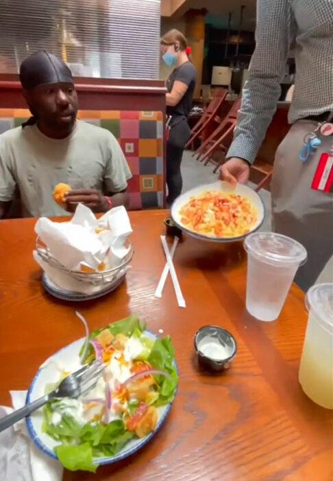 Hombre sin hogar comiendo en un restaurante junto a varias personas