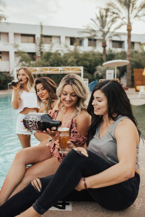 Chicas junto a una alberca bebiendo cerveza; Tomar cerveza podría disminuir el riesgo de Alzheimer estudio