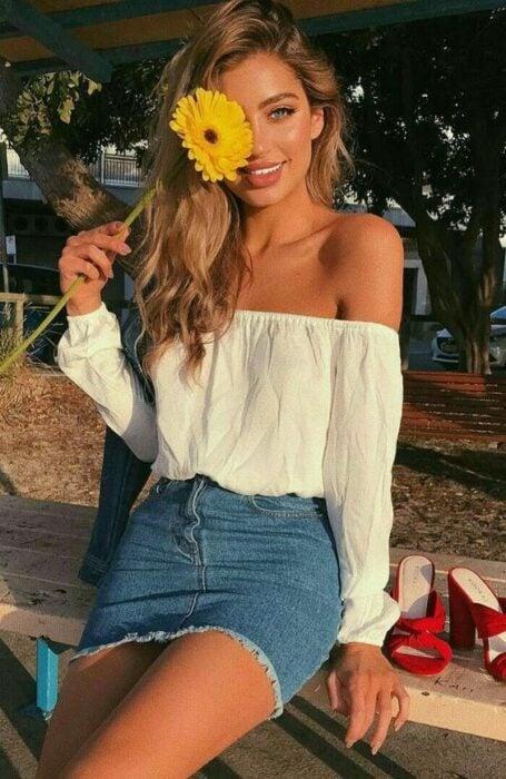 Chica posando para una fotografía mientras sostiene un girasol en sus manos