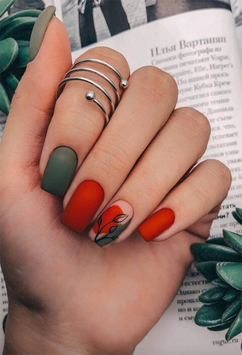 Manicure in red and green tonso, decorated with a sheet in black tone; Pretty nails with leaf design