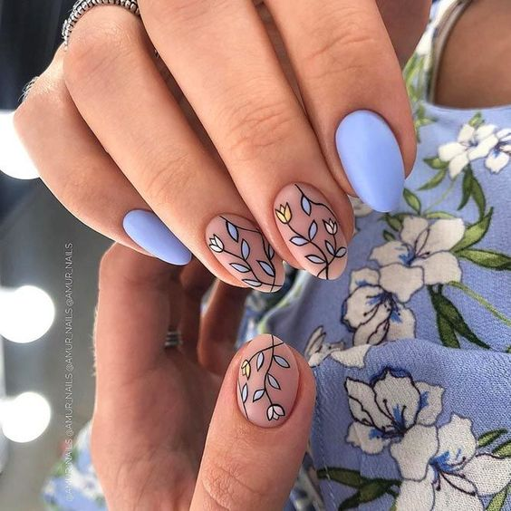 Manicure in pastel blue tone decorated with colored leaves; Pretty nails with leaf design