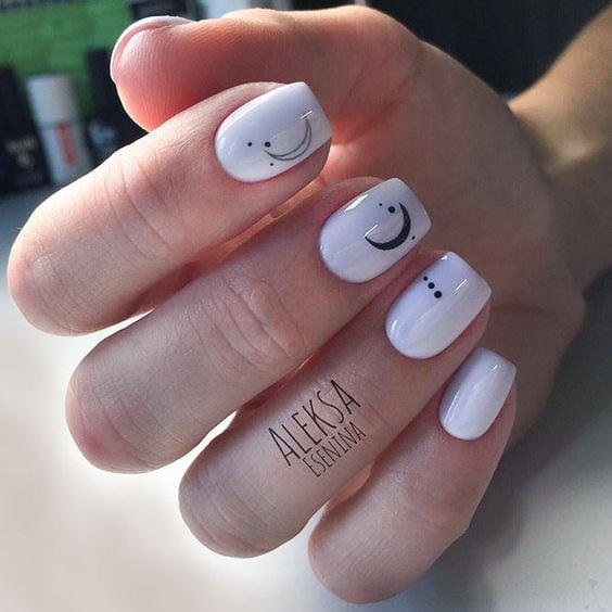 Manicura en tono blanco con luna y puntos negros; Uñas con lunitas que amarás
