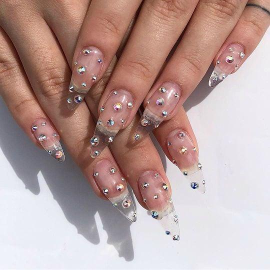 Diseño de uñas transparentes decoradas con estoperoles