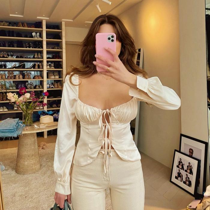 chica de cabello castaño usando una blusa beige de satén de manga larga con escote pronunciado y lazos al frente, jeans beige ajustados a la cintura
