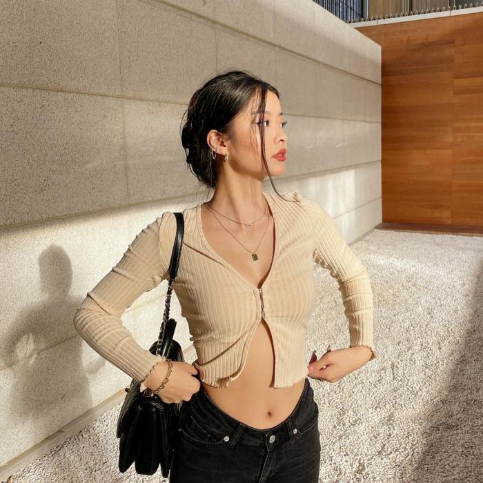chica de cabello oscuro lacio usando una blusa tipo camisa color champaña de botones con manga larga, jeans negros ajustados y bolso negro