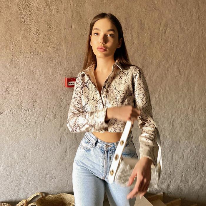 chica de cabello castaño usando una camisa crop top de satén con jeans claros y bolso blanco pequeño