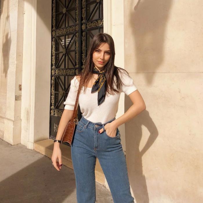 chica de cabello castaño usando una blusa blanca de manga 3/4, jeans ajustados a la cintura, bolsa café de cuero