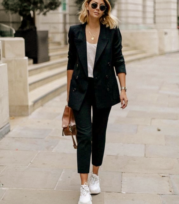blonde haired girl with sunglasses, white shirt, black suit, white tennis shoes, brown leather bag