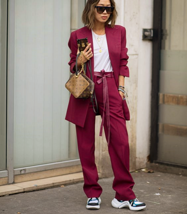 girl with short light hair wearing sunglasses, white t-shirt, fuchsia suit, white tennis shoes with black and blue, brown leather handbag