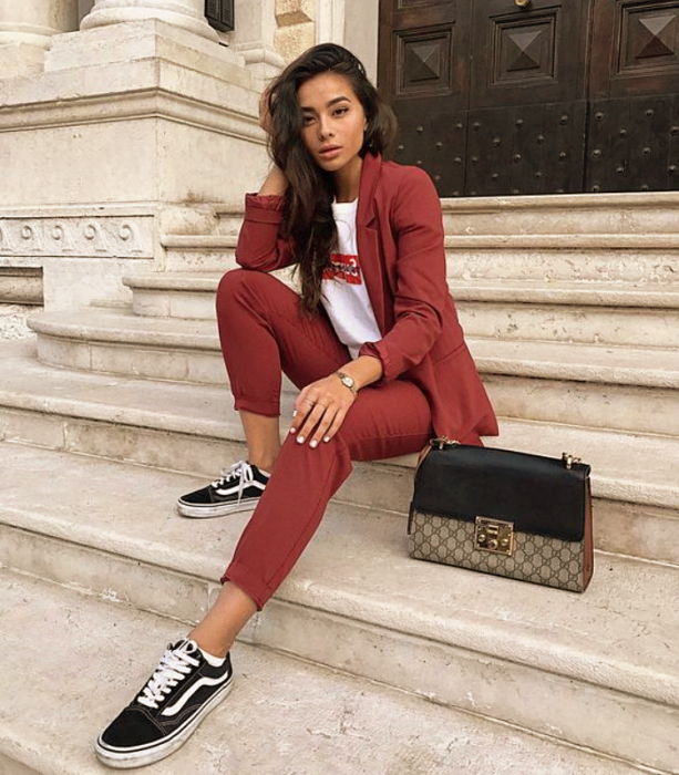 girl with long dark hair, white t-shirt with red logo, burnt red suit, black and white vans, brown tote bag with black leather