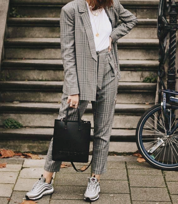 girl in gray suit, white t-shirt, gray tennis shoes with white, black leather bag