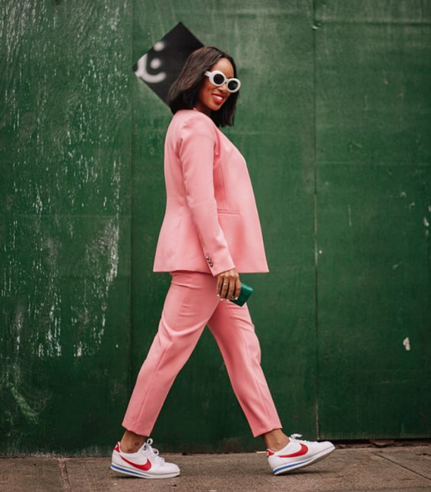 brunette girl with white sunglasses, pink suit, white tennis shoes with pink