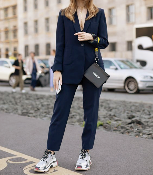 blonde girl in navy blue suit, white sneakers with gray and red, black leather handbag