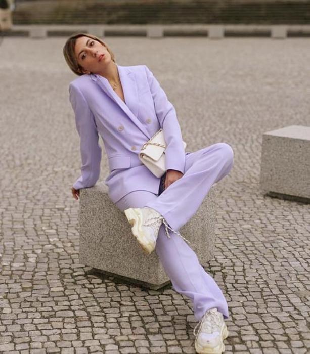 chica de cabello oscuro usando un traje color lila y tenis blancos, bolso blanco de cuero