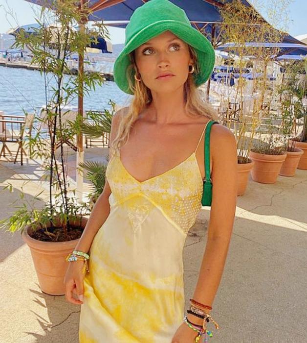 chica rubia con bucket hat verde, vestido de satén amarillo pastel de tirantes