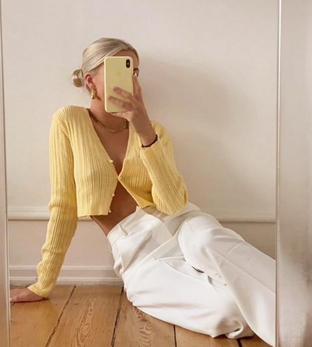 chica rubia platinada con cárdigan amarillo de manga larga, pantalones blancos de mezclilla holgados