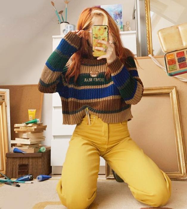 chica pelirroja con suéter de rayas azules, cafés, verdes y pantalones de mezclilla amarillos