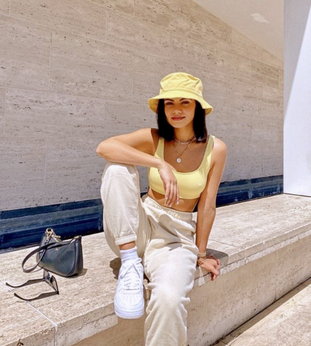 brown haired girl wearing yellow bucket hat, yellow tank top, baggy white pants and white tennis shoes