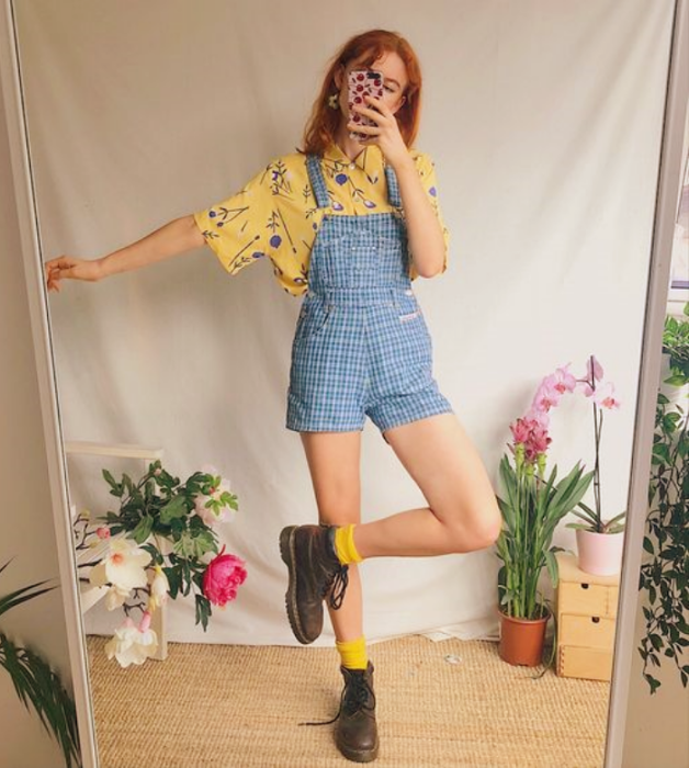 red-haired girl in a yellow shirt with little blue flowers, short denim overalls, brown ankle boots and yellow socks