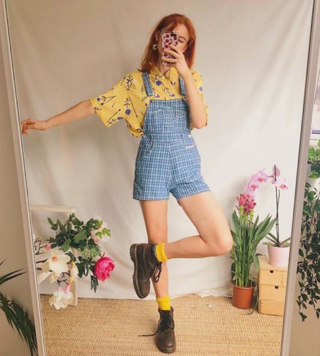 chica pelirroja con camisa amarilla con florecitas azules, overol de mezclilla corto, botines cafés y calcetines amarillos