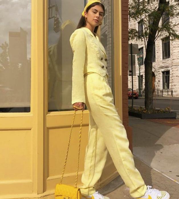chica de cabello castaño usando un saco blazer amarillo, pantalones de vestir amarillos, bolso de mano amarillo, tenis blancos