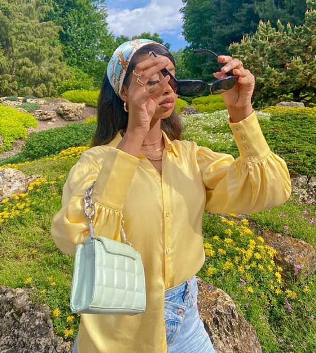 brunette girl with black sunglasses, yellow blouse with puffed sleeves, jeans at the waist with light blue bag